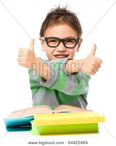 Cute little girl is reading a book and showing thumb up sign using both hands, isolated over white
