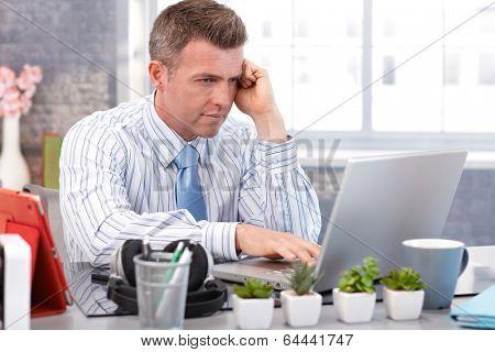Handsome businessman sitting at desk, using laptop computer.
