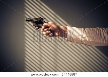 Man Pointing Revolver By Window