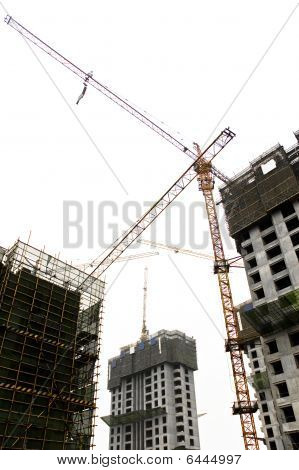 Construction Site Tower Cranes Against White Sky.
