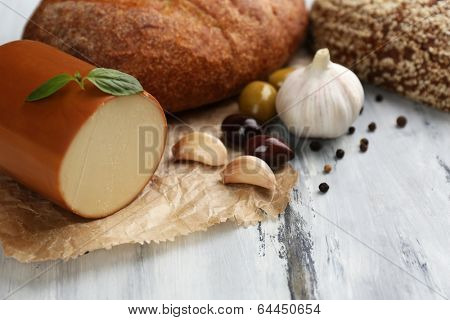 Tasty smoked cheese and bread on wooden table