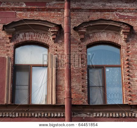 Two Windows And Drainpipe, On Red Brick Wall