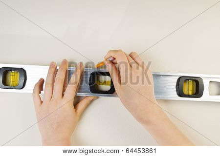 Measuring Level And Pencil For Marking Interior Wall