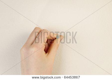 Placing Nail Against Interior Home Wall
