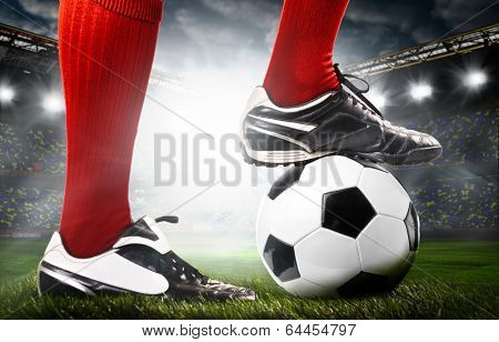 legs of a soccer or football player on ball on stadium