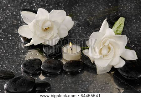 Spa still life with two gardenia flower and candle on pebbles
