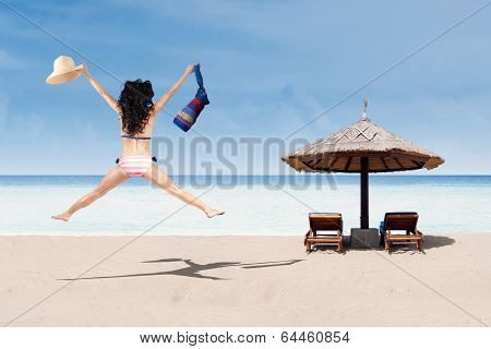 Excited woman jumping at beach