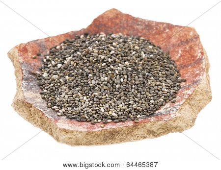 black chia seeds on an antique pottery shard isolated on white
