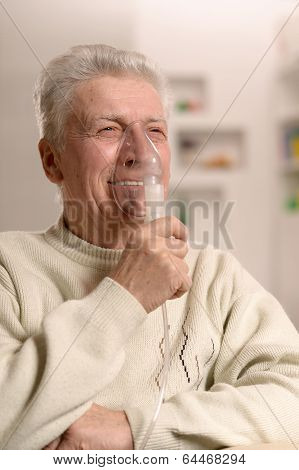 Elderly man making inhalation
