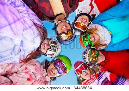 Seven happy friends in circle wearing goggles
