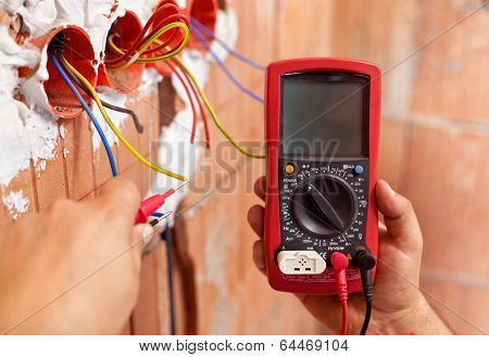 Electrician Hands With Multimeter And Wires