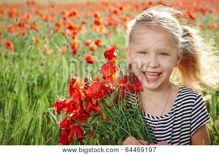 Happy laughing little girl  on the poppy meadow