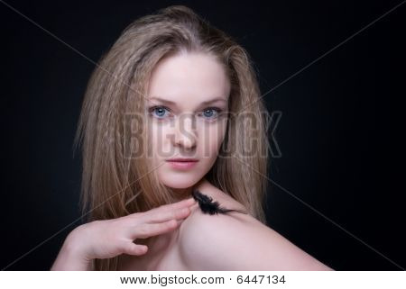 Close Up Portrait Of Blond Girl With Feather On Black