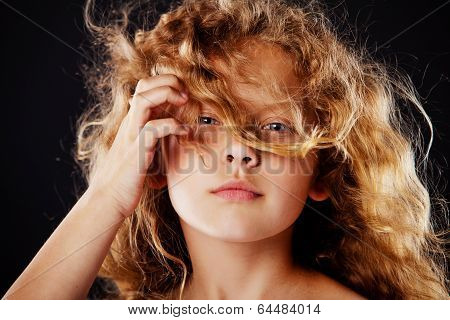 Portrait of beautiful little girl with windy hair. Fashion photo