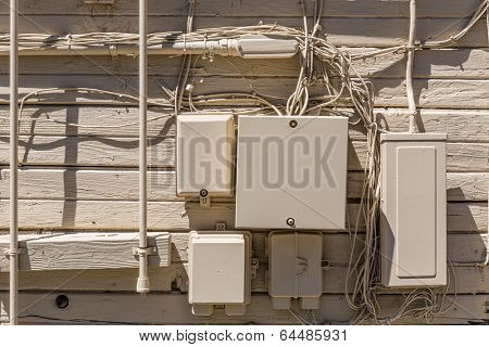 Messy cables and electrical boxes in a wooden beige painted wall facade