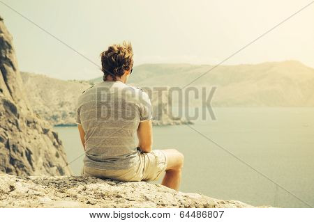 Young Man Relaxing On Rocky Cliff  Sea And Mountains On Background Lifestyle Summer Vacations Concep