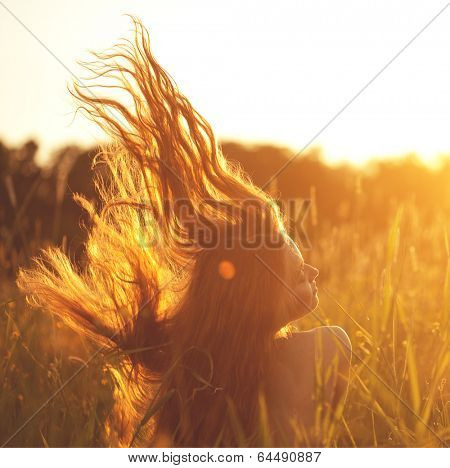 Beautiful smiling woman in a field at sunset. Trendy young girl at sunset with flying hair