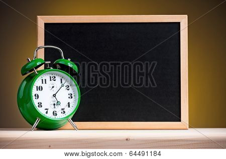 Big green alarm clock with blackboard on dark yellow background