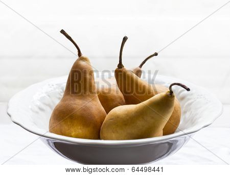 Golden organic pears in white bowl