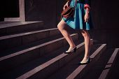 foto of up-skirt  - A young woman is walking up some stairs outside on a sunny day in the city - JPG
