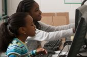 pic of young girls  - Kids learning how work on a computer