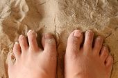 Image of women foot on sand.