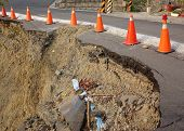 picture of landslide  - Red and white traffic cones mark a road that has been damaged by a landslide - JPG