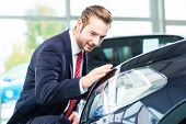 foto of showrooms  - Seller or car salesman in car dealership presenting the reflecting car paint of his new and used cars in the showroom - JPG
