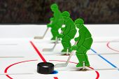stock photo of bandy stick  - Three hockey players in line with puck - JPG