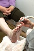 foto of chiropodist  - chiropodist at a senior woman at home - JPG