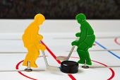 pic of bandy stick  - Two hockey players fight with puck in center - JPG