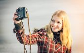 stock photo of swag  - Blonde Woman making self shot on her vintage retro camera happy smiling hipster Lifestyle winter time - JPG