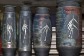 pic of raku  - A collection of four beautifully similar raku pots sitting on a shelf - JPG