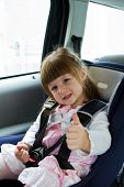 stock photo of seatbelt  - little cute girl sitting in the car in child safety seat and smiling - JPG