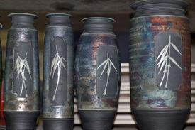picture of raku  - A collection of four beautifully similar raku pots sitting on a shelf - JPG