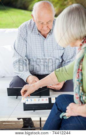 Senior couple playing Rummikub while sitting at nursing home