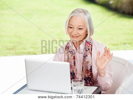 Smiling senior woman waving while video conferencing on laptop at nursing home porch