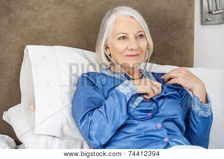 Senior woman listening to her heartbeat through stethoscope in bedroom at nursing home