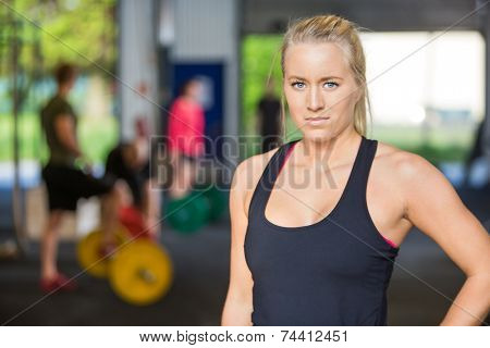 Portrait of confident young woman standing at cross-training center