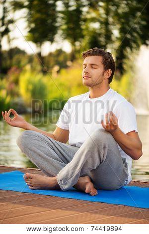 Young man maditating in lotus pose