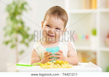 smiling kid boy eating indoors