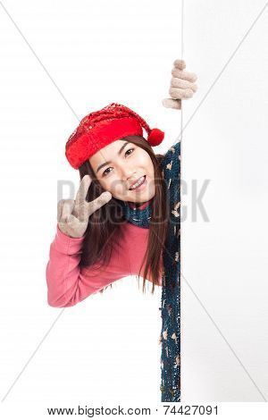 Asian Girl With Red Christmas Hat Peeking From Behind Blank Banner And Show V Sign