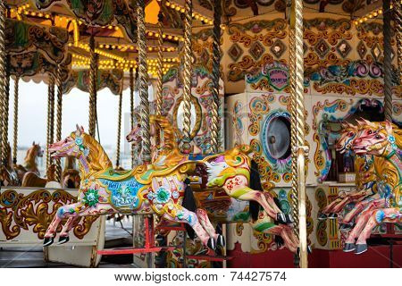 Brightly painted horses on a vintage carousel or merry-go-round at a fairground for children to ride as they go round and up and down imitating galloping
