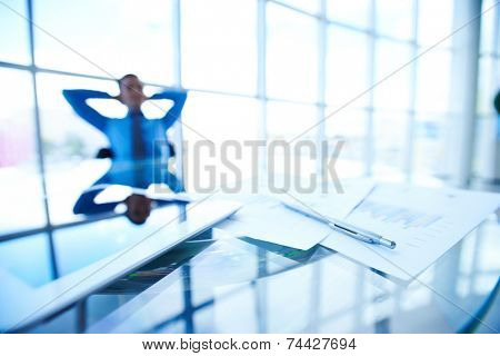 Business papers, touchpad and pen at workplace on background of restful manager