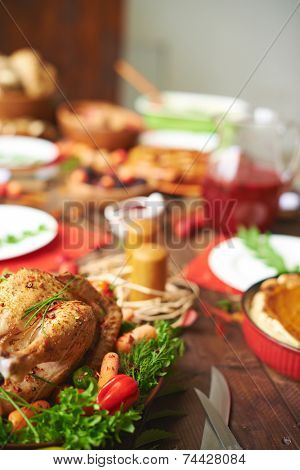Roasted turkey with pepper, carrots and greenery on festive table