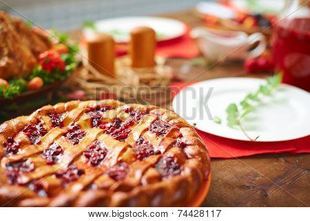 Homemade pie with cowberry jam on festive table