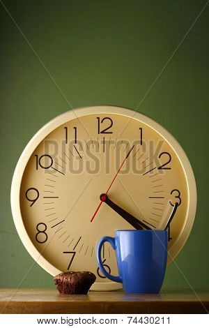 An analog clock, a blue coffee mug and a brownie