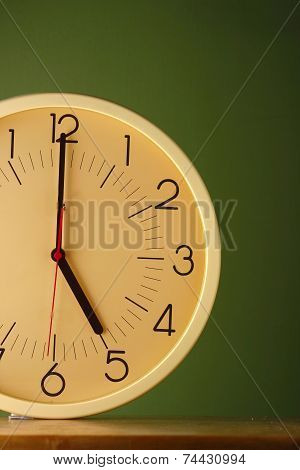An analog clock at five o'clock position