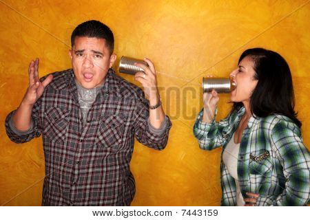 Hispanic Man And Woman Communicate Through Tin Cans