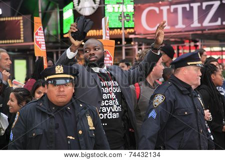 Marcher raising arms behind NYPD